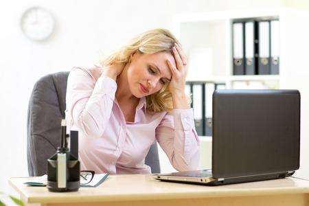 středního věku obchodnice s bolestí hlavy s stresu v kanceláři