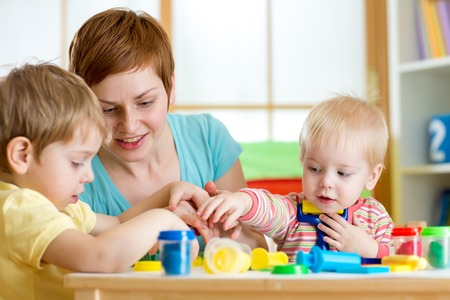 kids and woman play colorful clay toy indoor photo