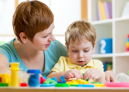 child boy and mother with playdough indoors photo
