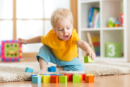 playing: kid toddler playing  wooden toys at home or nursery Stock Photo