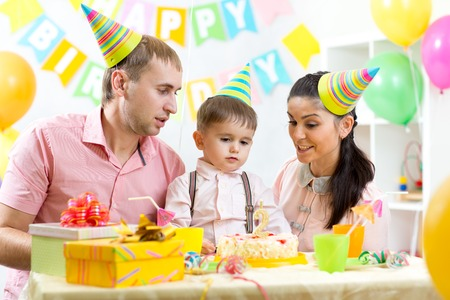 kid boy with parents blow candle on birthday cake photo