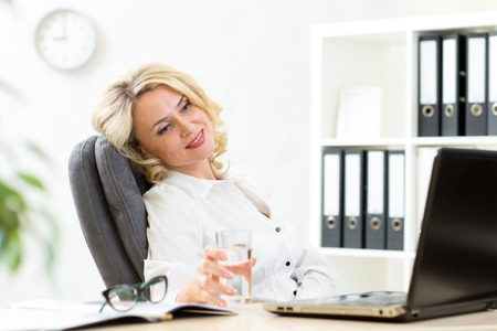middleaged: middle-aged businesswoman relaxing at work in office Stock Photo