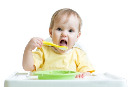 baby child eating healthy food with a spoon isolated