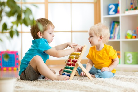 baby playing toy: children boys play with abacus toy indoors Stock Photo
