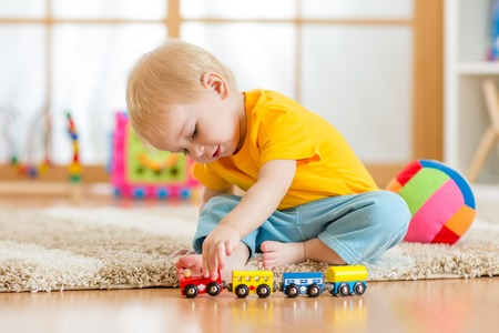 child boy playing with toys indoors at home