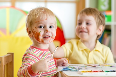 playschool: smiling kids boys paint at home or playschool