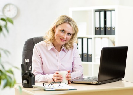 office documents: Cute blond mature businesswoman working on laptop and drinking coffee Stock Photo