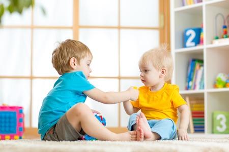 cute babies: ni�os jugando juntos en el piso en el hogar o cuidado de ni�os