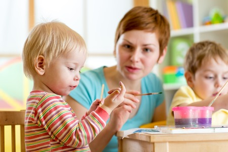 playschool: cute woman teaching children to paint at kindergarten or home or playschool Stock Photo