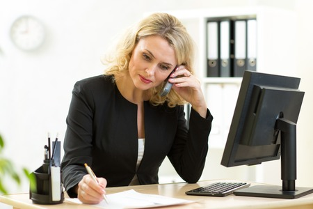 Middle-aged businesswoman working in office. Employee talking by phone and writing by pen Standard-Bild