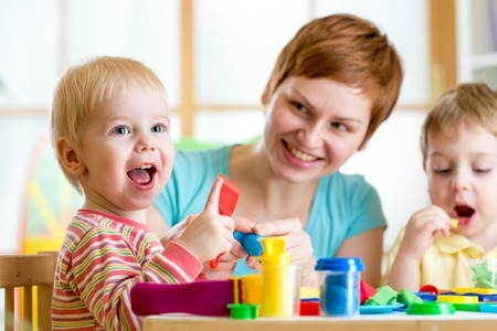 teaching: woman teaches kids handcraft at kindergarten or playschool Stock Photo
