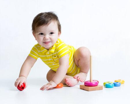 piramide humana: niño chico jugando con pirámide de juguete colorido Foto de archivo