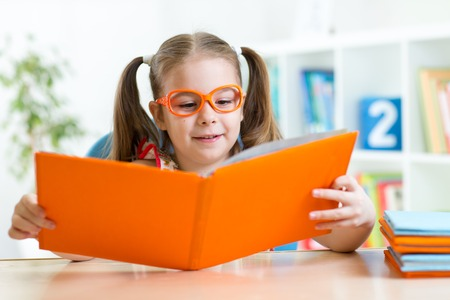 Child little girl reading a book at home or primary school