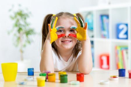 kinder spielen: Nettes fr�hliches Kind M�dchen zeigt ihre H�nde in hellen Farben gemalt Lizenzfreie Bilder
