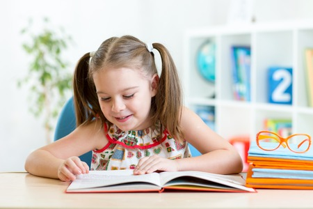 Child girl learns to read sitting at table in nursery