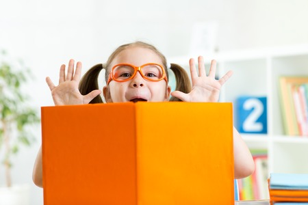kinder: chica divertida ni�o weared anteojos con libro en su casa o jard�n de infantes