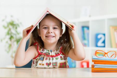 preschool children: preschooler child girl with book over her head at home