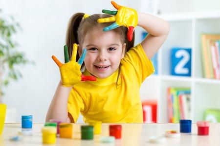 Enfant fille drôle avec les mains peintes en peinture colorée à la maison Banque d'images - 36147333