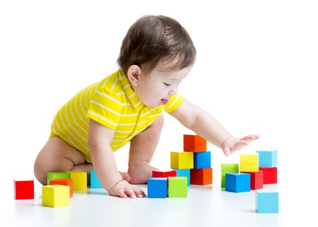 tower block: kid boy playing  wooden toy blocks isolated