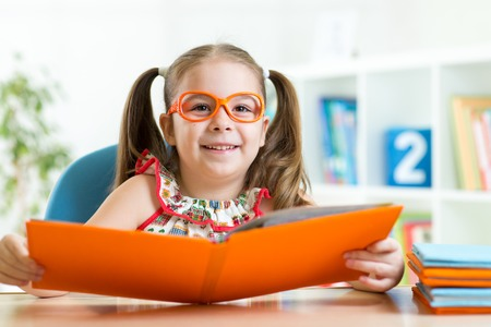 intelligently: clever cu te child girl wered eyeglasses with book in primary school or home