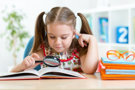 hyperopia: cute kid girl looks through a magnifying glass with book sitting at table