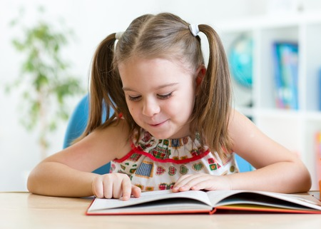 education concept - smiling little student kid reading book at home
