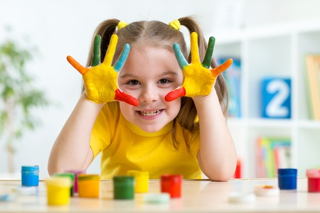 Portrait of child girl with face and hands painted at home Foto de archivo