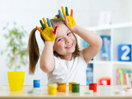 Portrait of cute little girl with painted palms