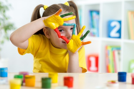 cute kid girl have fun painting her hands Stock Photo