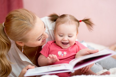 reading: happy mother read a book to child girl indoors Stock Photo