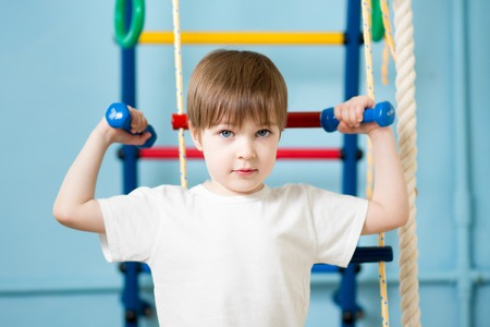 kids exercise: Strong kid boy exercising with dumbbells. Healthy life, sport. Stock Photo