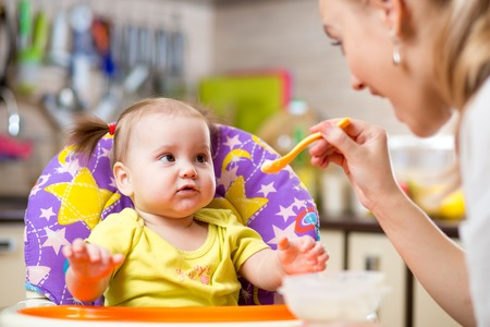 Happy mother spoon feeding child toddler indoors photo