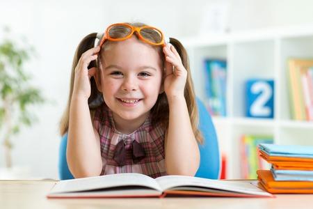 Happy funny kid girl in eyeglasses reading a book in primary school