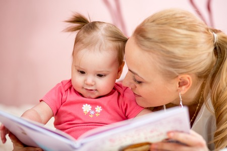 happy mother read a book to baby girl indoors