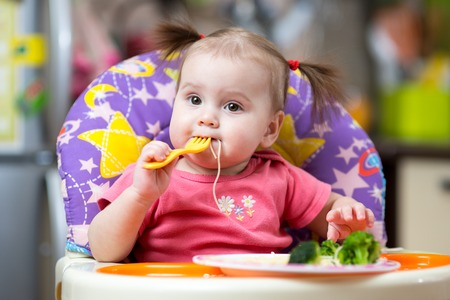 toddler girl in a highchair for feeding with fork and plate at home Foto de archivo