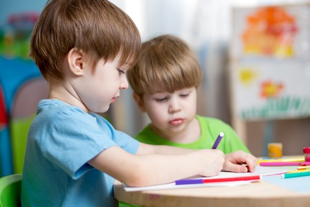 childcare: children boys painting in nursery at home Stock Photo