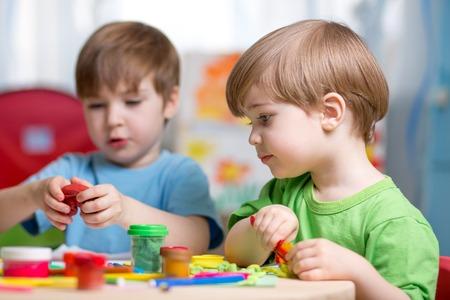 ni�os jugando en la escuela: ni�os jugando con plastilina en casa o jard�n de infantes o guarder�a Foto de archivo