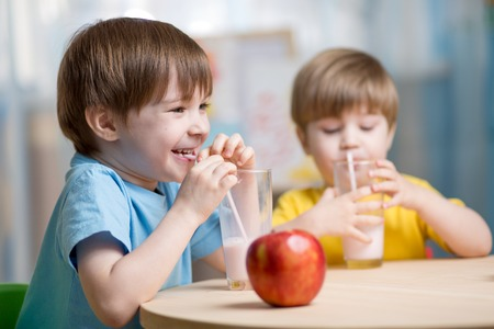eating lunch: kids drinking milk at home at home or kindergarten