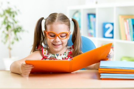 hyperopia: Happy funny kid girl in eyeglasses reading a book Stock Photo