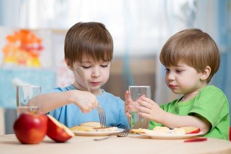 ni�os desayuno: ni�os comiendo y bebiendo en casa o el jard�n de infantes