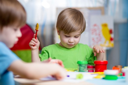 playschool: kids playing with play clay at home or  playschool