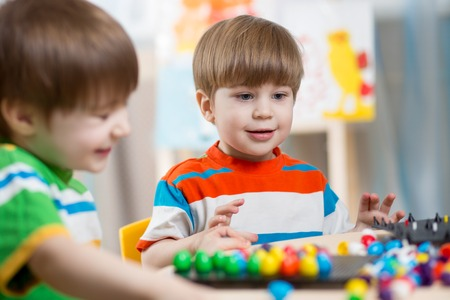 fingers put together: happy children brothers play together at table Stock Photo