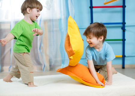 pillow fight: kids boys have fun playing with pillows at home Stock Photo
