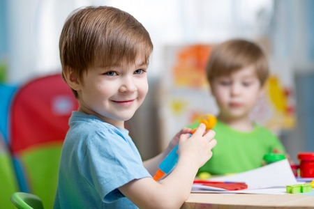 school activities: kids playing with play clay at home or  playschool