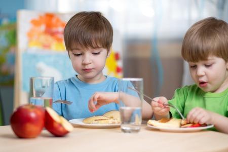 tomando agua: ni�os comiendo alimentos saludables en el hogar o el jard�n de infantes
