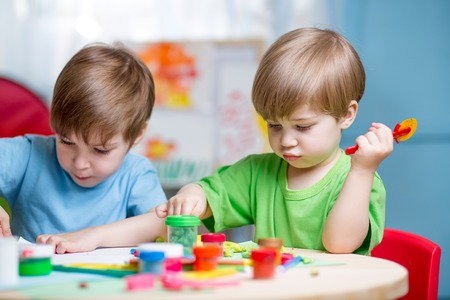 learning materials: kids boys playing with plasticine at home Stock Photo