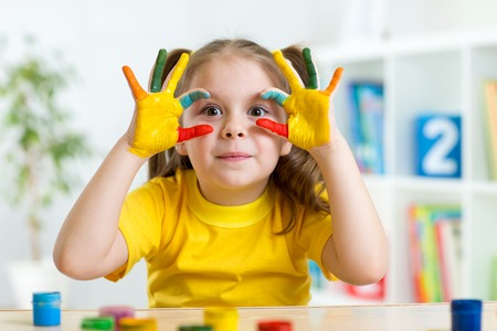 cute child girl have fun painting her hands photo