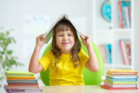 preescolar: Chica ni�o en edad preescolar con el libro sobre su cabeza en el interior Foto de archivo