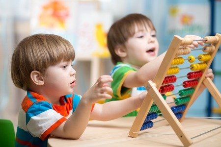 abaco: los niños felices los niños jugando con el juguete ábaco en interiores Foto de archivo