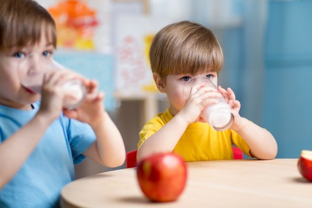 drinking milk: children eating healthy food at home or kindergarten